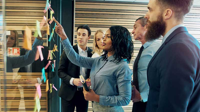 Businesswoman leading a team meeting going over post-it-notes stuck on a glass window